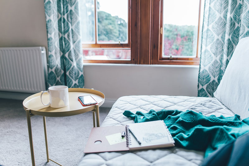 Comfy chair with a notebook, teal blanket and coffee mug